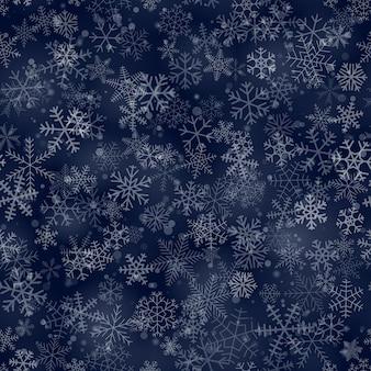 Padrão sem emenda de natal de flocos de neve de diferentes formas, tamanhos e transparência, em fundo azul escuro