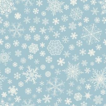 Padrão sem emenda de natal de flocos de neve grandes e pequenos, branco sobre azul claro