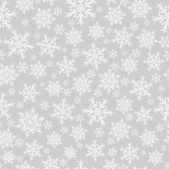 Padrão sem emenda de natal de flocos de neve grandes e pequenos, branco sobre cinza