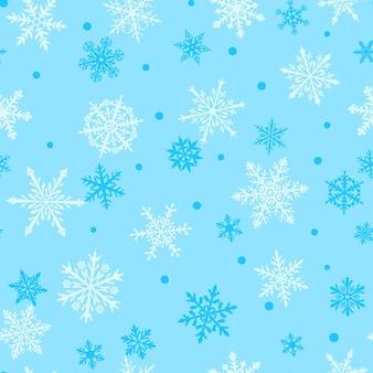 Padrão sem emenda de natal de flocos de neve grandes e pequenos complexos em cores brancas sobre fundo azul claro
