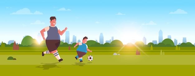 Pai com filho jogando futebol sobre tamanho família se divertindo no gramado verde na atividade de perda de peso do parque