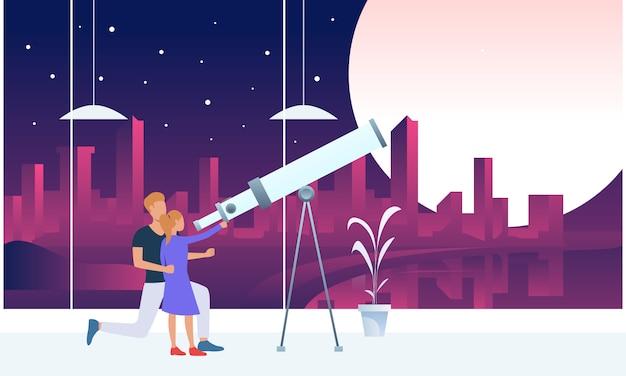 Pai e filha olhando a lua através do telescópio