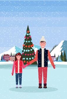 Pai e filha patinando na pista de gelo com árvore de natal decorada no hotel resort de esqui