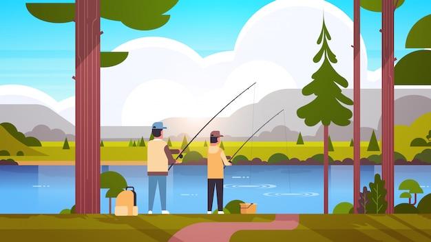 Pai e filho pescando junto vista traseira homem com menino usando varas feliz família fim de semana fisher conceito passatempo montanhas paisagem paisagem fundo liso comprimento total horizontal