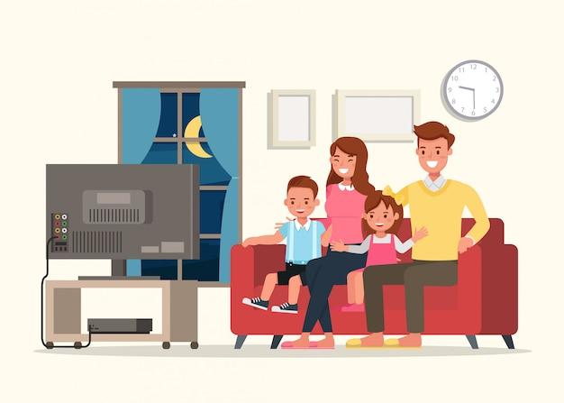 Pai mãe e filhos assistindo televisão.