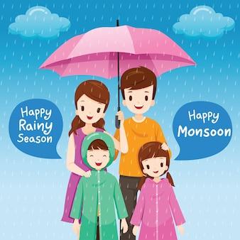 Pais e filhos sob o guarda-chuva juntos na chuva, crianças vestindo capa de chuva, feliz dia de chuva