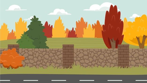Paisagem com uma cerca de pedra em primeiro plano, arbustos e árvores.