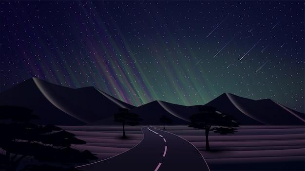 Paisagem da noite com uma estrada no deserto com dunas de areia, árvores, céu estrelado, luzes do norte verdes e montanhas no horizonte.