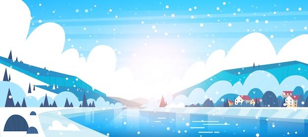 Paisagem de inverno de pequenas casas de aldeia em bancos de rio congelado e montes de montanha coberta com sn