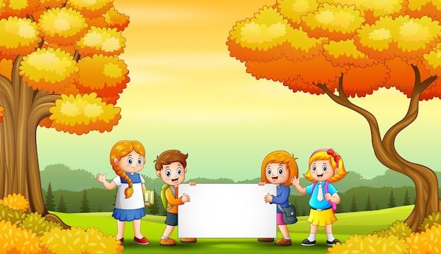 Paisagem de outono com crianças em idade escolar segurando cartazes em branco