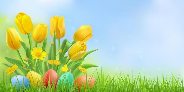 Paisagem de páscoa com tulipas amarelas e ovos de páscoa coloridos