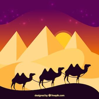 Paisagem de pirâmides egípcias com caravana de camelos