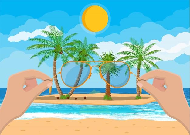 Paisagem de praia, mão com óculos de sol.