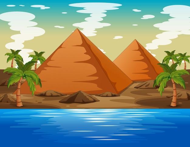 Paisagem desértica com pirâmide e lago