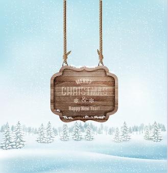 Paisagem do inverno com um sinal de feliz natal ornamentado de madeira.