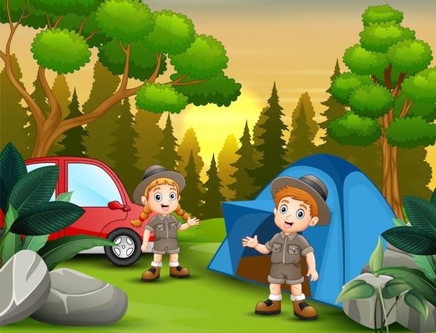 Paisagem do por do sol com as crianças do explorador no acampamento
