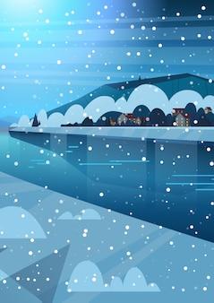 Paisagem noturna de casas de aldeia de inverno perto de colinas de montanha e rio congelado ou lago