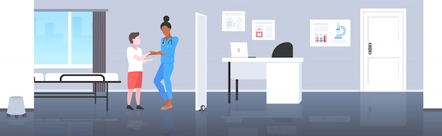 Palavras-chave: pediatra médico menino paciente paciente mulher uniforme uniforme conceito miúdo médico consulta conceito moderno hospital pediátrico hospital quarto interior comprimento horizontal