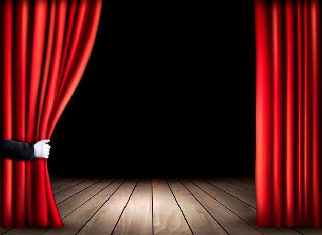 Palco de teatro com piso de madeira e cortinas vermelhas abertas. .
