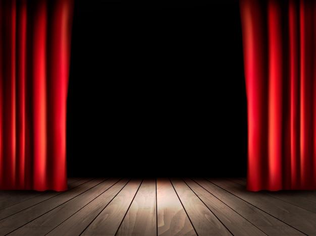 Palco de teatro com piso de madeira e cortinas vermelhas.