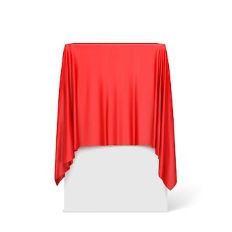 Pano vermelho em um pedestal quadrado isolado no branco.