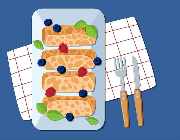 Panquecas finas em um prato com frutas são servidas com garfo e faca no azul