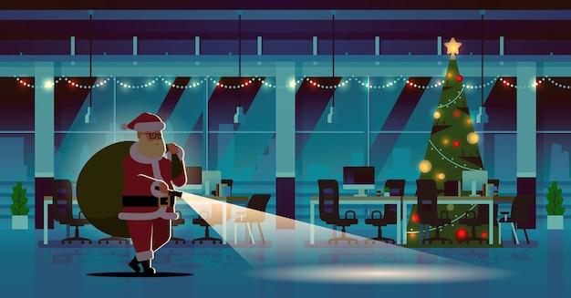 Papai noel com saco de presentes usando lanterna natal ano novo feriados celebração conceito noite moderna decorado escritório interior ilustração plana