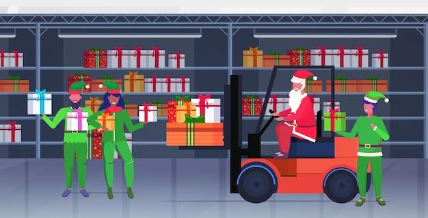Papai noel dirigindo empilhadeiras com duendes segurando caixas de presentes coloridas feliz natal feliz ano novo