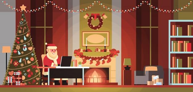 Papai noel na sala de estar decorada para o feriado de ano novo de natal usando laptop pinheiro lareira casa interior conceito plana horizontal