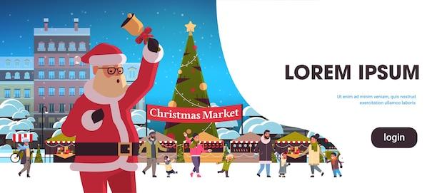 Papai noel segurando o sino do mercado de natal, feira de férias, com pinheiros, pessoas caminhando perto de barracas, banner de celebração de feriados de natal feliz