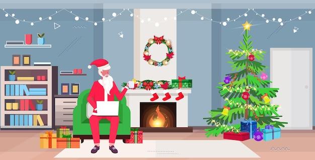 Papai noel sentado na poltrona usando laptop e bebendo chá. sala de estar moderna com lareira, abeto e caixas de presente. conceito de celebração de feriados de ano novo.
