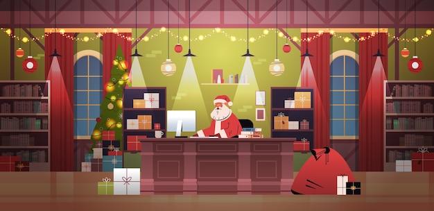 Papai noel sentado no local de trabalho e usando o computador. feliz natal, feliz ano novo, feriados, celebração, conceito, decorado, interior, escritório, horizontais