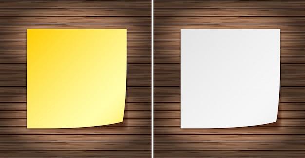 Papéis amarelos e brancos em branco na parede de madeira