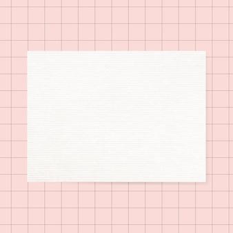 Papel de carta branco em branco sobre fundo de grade rosa
