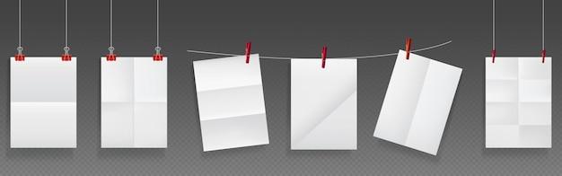 Papel dobrado pendurado em corda e alfinetes, folhas de papel branco em branco de textura enrugada.