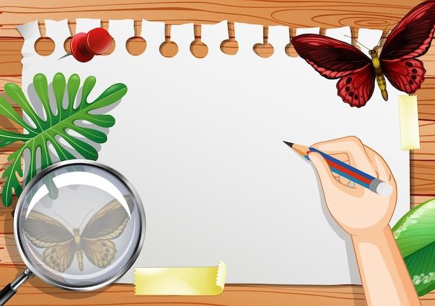 Papel em branco na vista de cima da mesa com folhas e elementos de borboleta