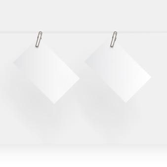 Papel em branco pendurado realista simulado acima com clipe de papel dourado