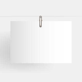 Papel horizontal em branco pendurado realista simulado acima com clipe de papel dourado