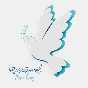 Papel recorte pombo com símbolo da folha da paz. dia internacional da paz