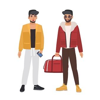 Par de homens caucasianos vestindo roupas casuais e bonés, segurando o telefone e a bolsa, conversando
