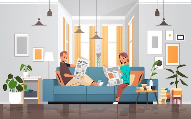 Par, segurando, jornais, homem, mulher, sentando, sofá, leitura diária, notícia, imprensa, mídia, conceito