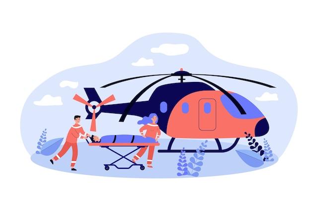 Paramédicos levando maca com uma pessoa para o helicóptero da ambulância.