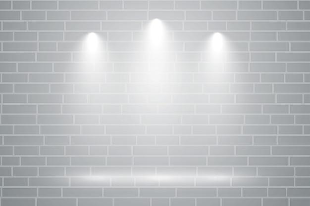 Parede cinza com três focos de luz caindo sobre ela