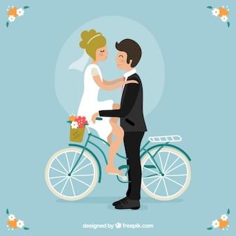 Pares bonitos do casamento em uma bicicleta