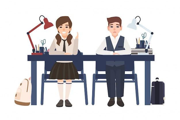 Pares de menino e menina de escola no uniforme que senta-se na mesa no fundo branco.