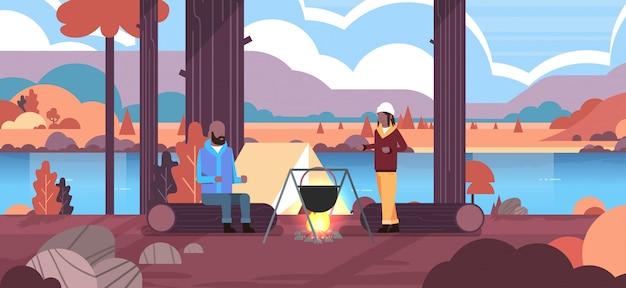 Pares, hikers, homem, mulher, cozinhar, refeições, em, coco, fervendo, panela, em, fogueira, acampamento, barraca, conceito, outono, paisagem, natureza, rio, montanhas, fundo, horizontal