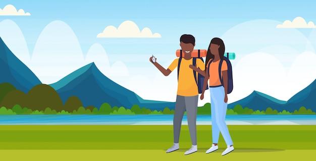 Pares turistas hikers usando bússola procurando sentido homem conceito mulher afro-americana viajantes em hike montanhas paisagem fundo comprimento horizontal horizontal