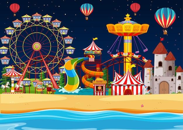 Parque de diversões com cena à beira-mar à noite e balões no céu
