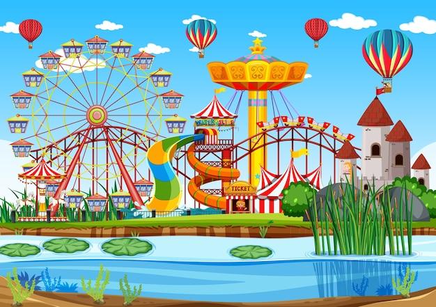 Parque de diversões com cena de pântano durante o dia e balões no céu