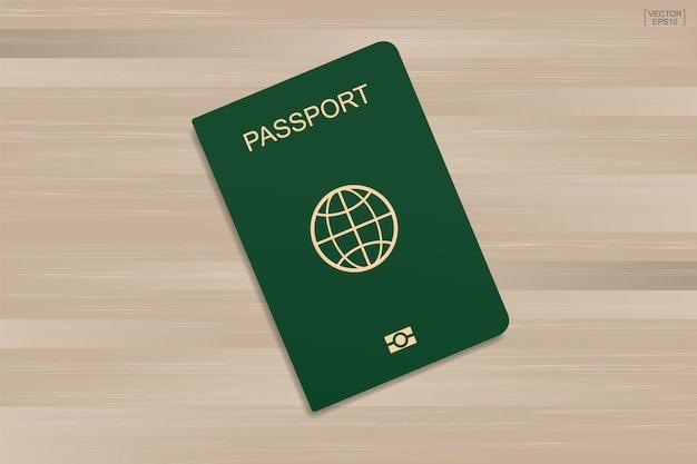 Passaporte verde no teste padrão e no fundo de madeira da textura.